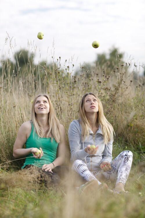 happy girls juggling apples in a field