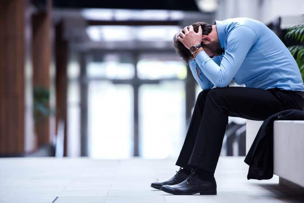Professionally dressed man sitting down looking stressed - how to avoid Management Liability