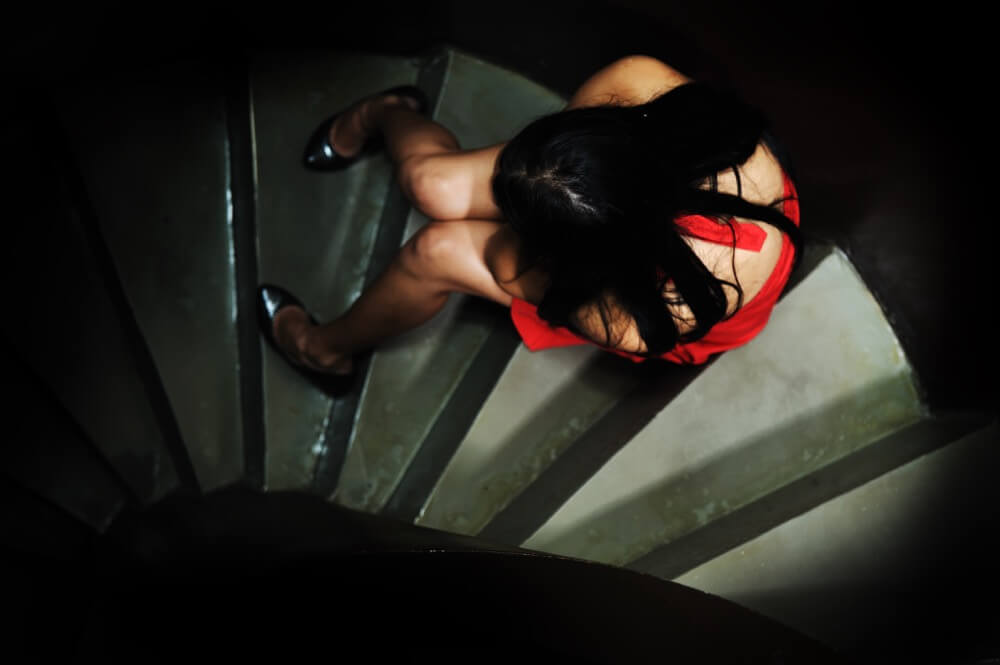 Girl on Steps crying in the dark- Preventing sexual harassment in the workplace