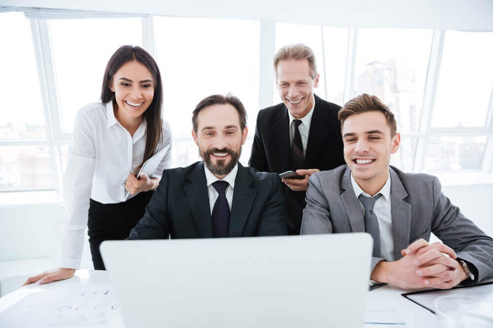 4 professionally dressed office staff smiling at what is on computer screen. Image used in why have a fully managed LMS