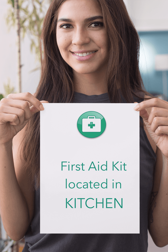 Person holding up sign that says the first aid kit is located in the kitchen